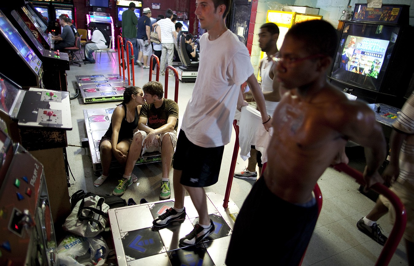 From left, Rebecca Curtis kisses Michael Thomas as Peter Kokolis and Andre Scott play a dance game at the Chinatown Fair video arcade on Mott Street in New York, July 17, 2010. The arcade is one of the last traditional arcades in the city where hard-core gamers still play face-to-face. (Michael Nagle/The New York Times)