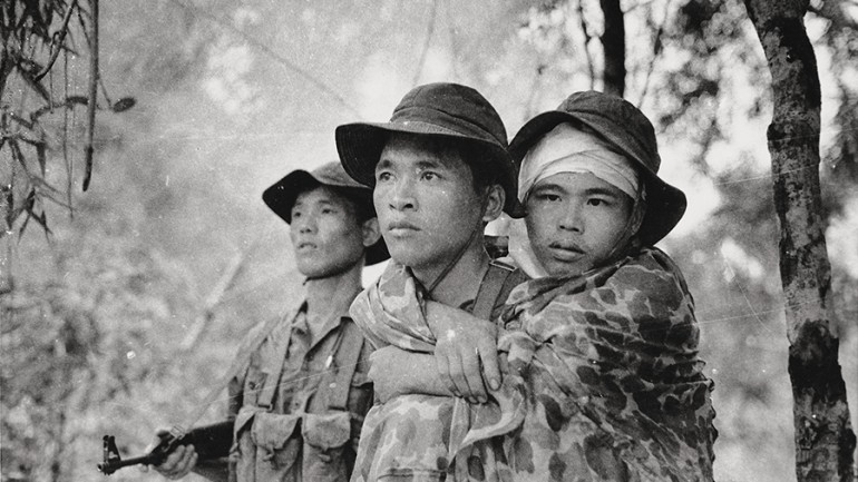 Viet Cong soldier carries a wounded friend