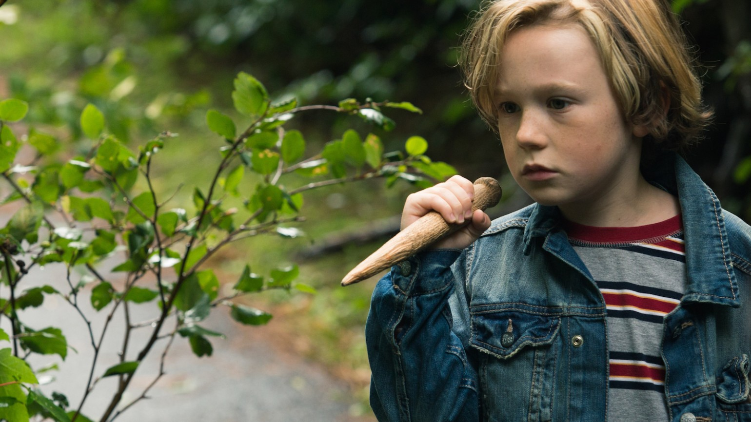 A hesitant Oscar (Jack Fulton), with stake in hand, follows a group of bullies into a graveyard.