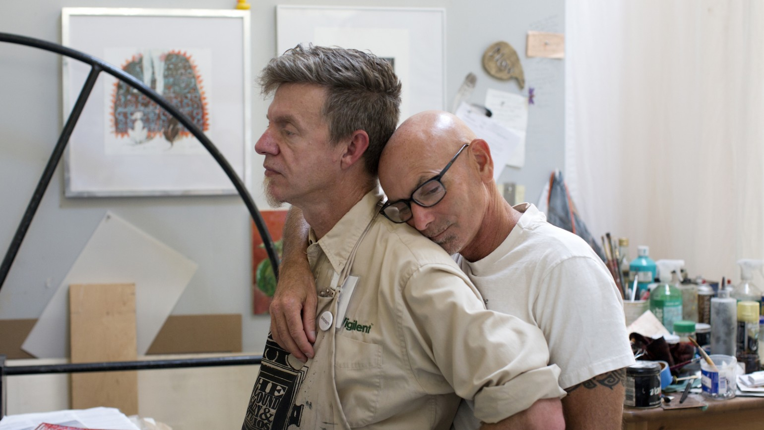 Ralph Thurlow kisses his husband, David Spiher, on the back during a visit to Spiher's artist studio in Oakland, Calif. on September 10, 2015. Both men are HIV-positive and Thurlow has AIDS-related dementia. (Photo by Erin Brethauer)
