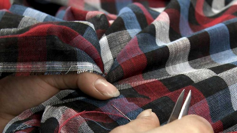 A migrant worker repairs fabric in a weaving factory in Changzhou, China.